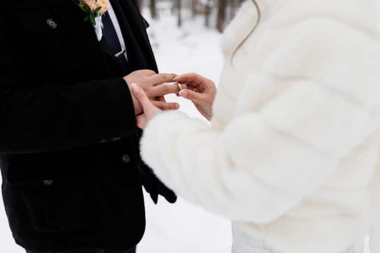 Winterhochzeit Braut steckt Ehering an Bräutigam Hochzeitsplaner München