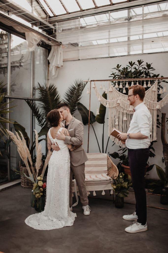Freie Trauung Boho Hochzeitskonzept nachhaltig heiraten Hochzeit Trauredner Makramee Traubogen Brautpaar Kuss